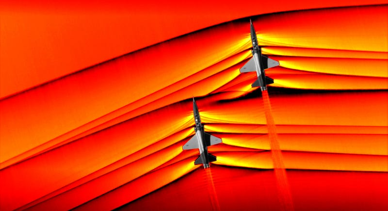 The shockwaves from two T-38 aircraft are seen interacting in this stunning photo. The images were originally monochromatic, and are shown here as a colorized composite image.