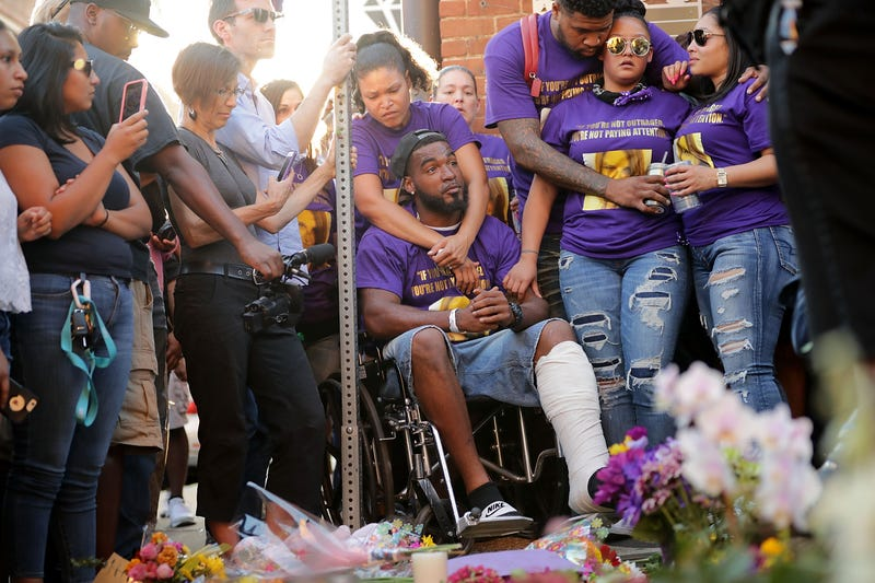 Marcus Martin (C), who was injured when a car plowed into a crowd of people protesting against the white supremacist Unite the Right rally, his fiancée Marissa Blair (behind with arms around Marcus) and friends visit the memorial built at the place where he was injured and where where 32-year-old Heather Heyer was killed in the same attack August 13, 2017 in Charlottesville, Virginia. (Photo by Chip Somodevilla/Getty Images)