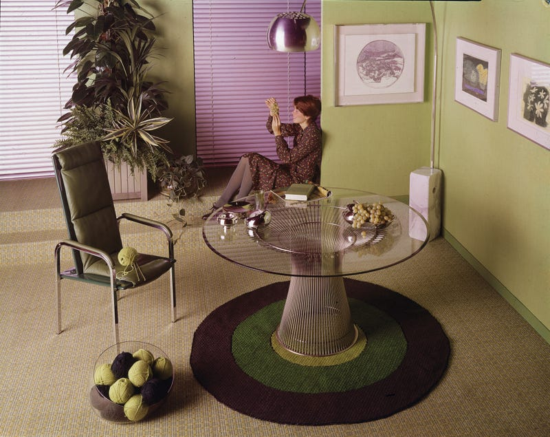 """""""A smiling short-haired woman in a print dress sits on the floor by the window and admires a bunch of grapes in a green dining room with one chair and a table with a glass top, 1970s."""" Via Getty."""