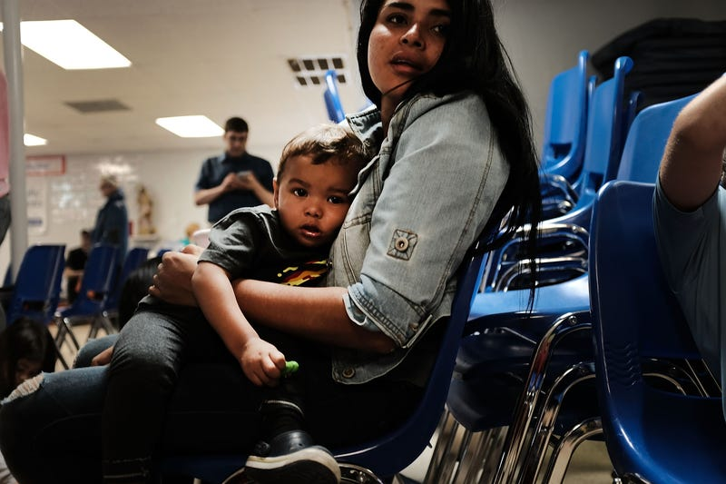 A woman who idendtified herself as Jennifer sits with her son Jaydan at the Catholic Charities Humanitarian Respite Center after recently crossing the U.S., Mexico border on June 21, 2018 in McAllen, Texas