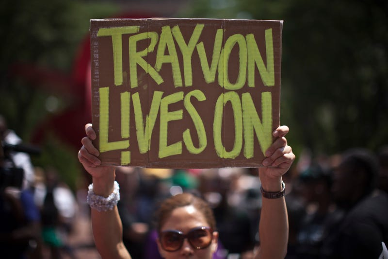 A woman holds a sign as she attends a rally honoring Trayvon Martin organized by the National Action Network outside One Police Plaza in Manhattan on July 20, 2013 in New York City.