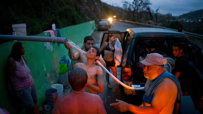 People bathe in and collect water piped from a creek in the mountains, in Naranjito, Puerto Rico, Thursday, Sept. 28, 2017. Image via the AP.