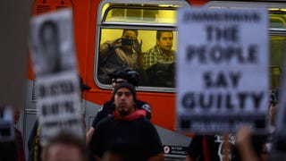 A passenger on a city bus observes a march in downtown Los Angeleson July 16, 2013, protesting the acquittal in Florida of George Zimmerman in the shooting death of Trayvon Martin.Kevork Djansezian/Getty Images