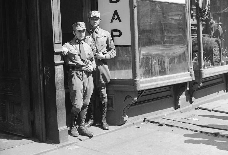 Two American Nazis in uniform stand in the doorway of their newly opened headquarters in the Yorkville section of New York City on April 1, 1932.