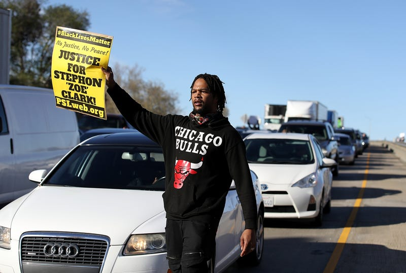 A Black Lives Matter protester holds a sign as he marches on Interstate 5 during a demonstration on March 22, 2018, in Sacramento, Calif.