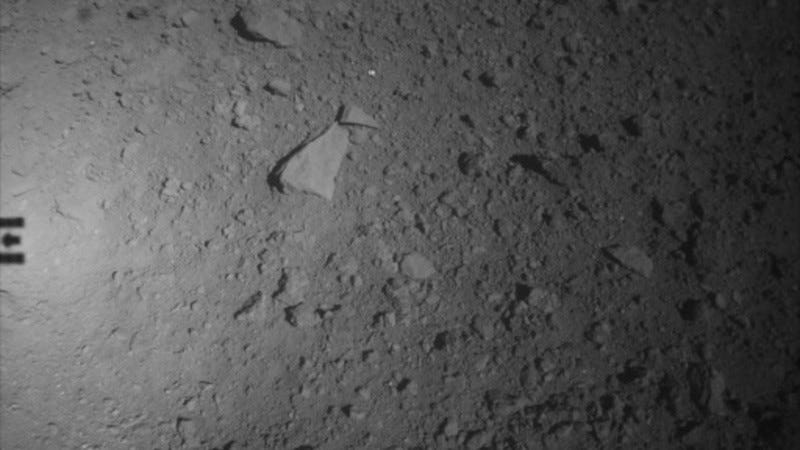 A view of Ryugu's surface, with the shadow of Hayabusa 2 seen at far left.