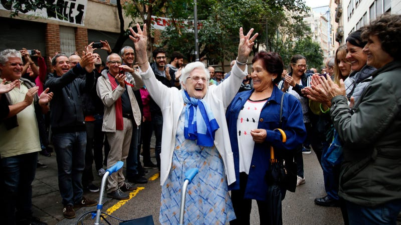 Woman applauded for voting at Catalan polling place on October 1st. Image via AP.