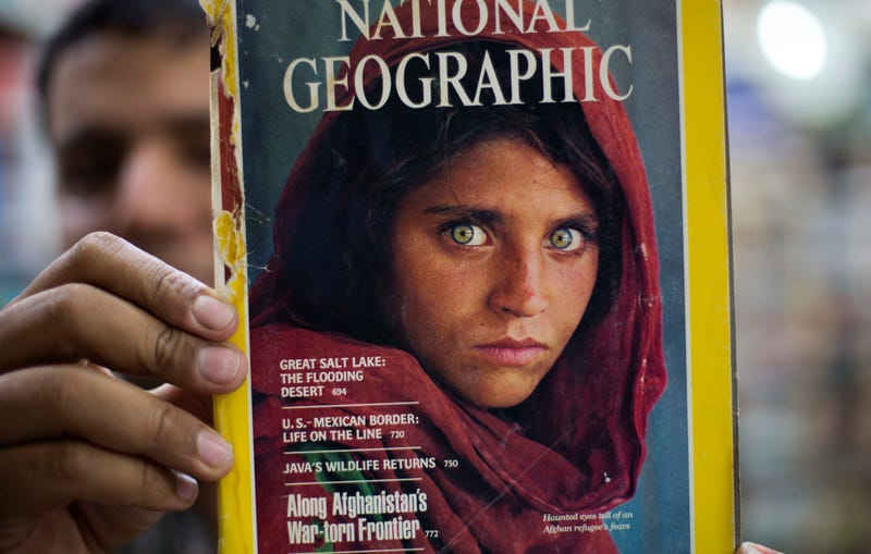 In an Oct. 26, 2016 photo, the owner of a book shop in Islamabad, Pakistan, shows a copy of a National Geographic magazine with a photo of Sharbat Gulla, an Afghan refugee, on the cover.