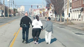 Lt. Aubrey Gregory, Asia Ford and Ford's son Terrance walk the last miles of the Rodes City Run, a 10K race in Louisville, Ky., March 21, 2015. Facebook