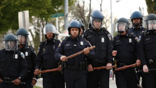 Police officers in riot gear walk toward protesters along Reisterstown Road near Mondawmin Mall in Baltimore April 27, 2015.DREW ANGERER/GETTY IMAGES