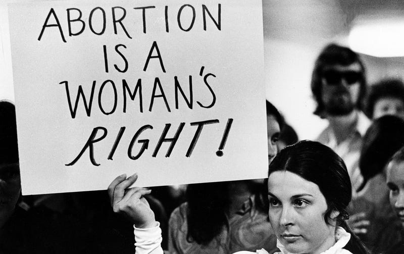 A young woman holds a sign demanding a woman's right to abortion at a demonstration to protest the closing of a Madison abortion clinic in Madison, Wis., April 20, 1971. Photo via AP