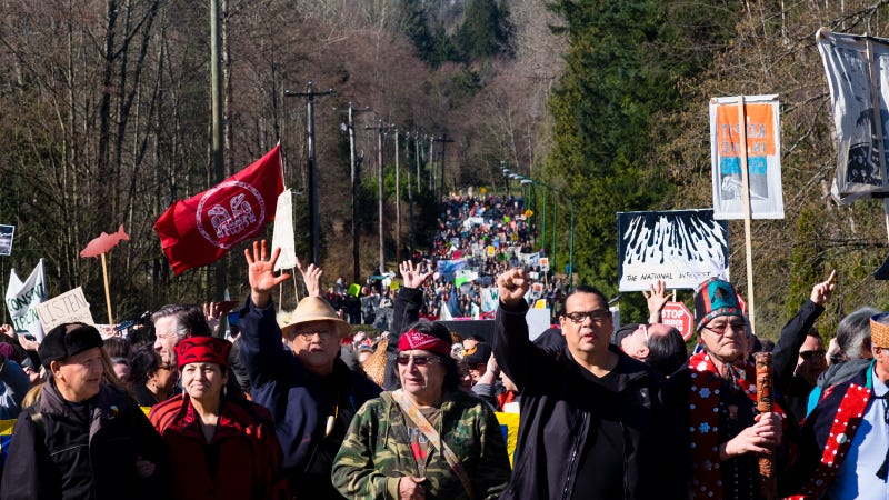 Tseil Waututh Chief Reuben George (second from right) raises a fist while leading a protest against Kinder Morgan's Trans Mountain Pipeline expansion.