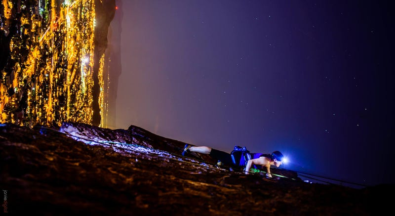 Illustration for article titled Spectacular photo of a woman climbing a vertical rock wall at night