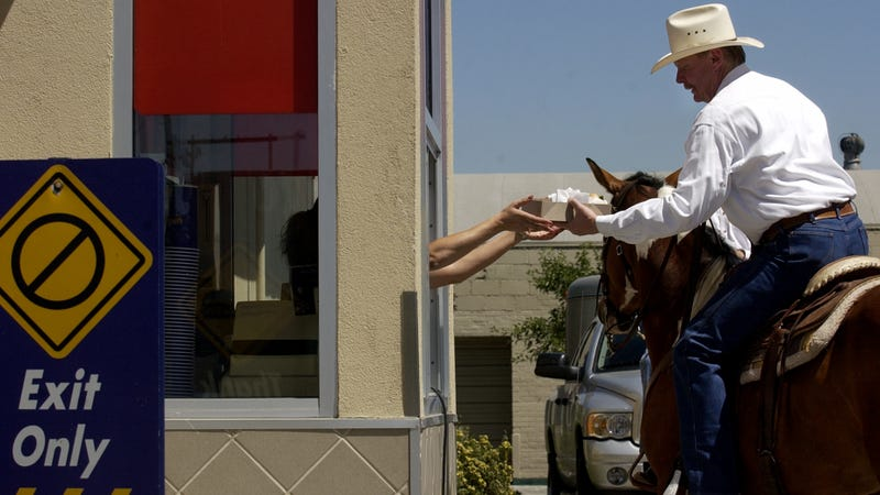 Mel Coleman, chairman of Coleman Natural Meats, sits atop a horse as he receives a hamburger from the drive-through window at Good Times Burgers & Frozen Custard in Denver, Colorado.