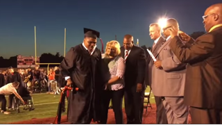 Micah McDade walks across the stage to receive his high school diploma from Okmulgee (Okla.) High School May 20, 2016. YOUTUBE VIA OKMULGEE TV