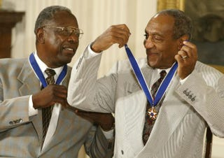 Bill Cosby (right) jokes with baseball great Hank Aaron after they both received the Presidential Medal of Freedom from President George W. Bush during a ceremony at the White House July 9, 2002.Mark Wilson/Getty Images