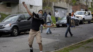 A youth throws a rock at police on April 27, 2015, in Baltimore. Violent street clashes erupted in Baltimore after friends and family gathered for the funeral of Freddie Gray, a 25-year-old black man whose death in custody triggered a fresh wave of protests over U.S. police tactics.  Brendan Smialowski/AFP/Getty Images