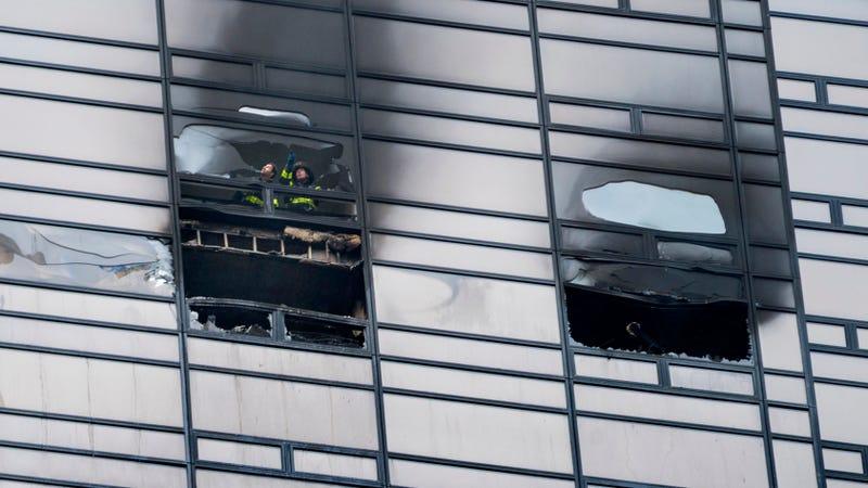 Dos bomberos inspeccionan una ventana rota tras apagar el incendio del 7 de abril de 2018 en un apartamento de la Torre Trump