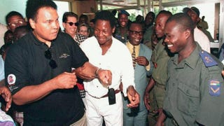 Former world heavyweight champion Muhammad Ali jokes with boxing champion Augustin N'Gou and soldiers upon his arrival in Abidjan, Côte d'Ivoire, Aug. 18, 1997.Jean-Philippe Ksiazek/AFP/Getty Images