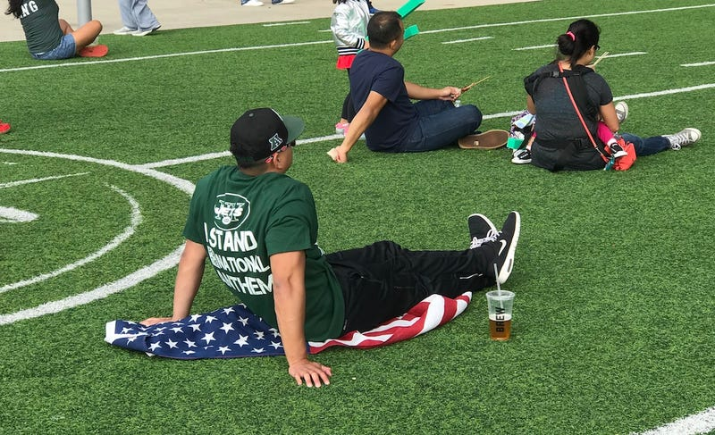 Illustration for article titled Jets Fan Who Stands For National Anthem Sits On American Flag