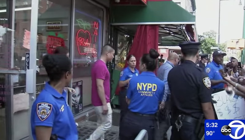 NYPD officers escort salon workers out of the salon following protests