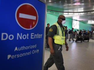 An airport worker wears a protective face mask in the arrivals area of Los Angeles International Airport as the U.S. announced increased passenger screenings against the Ebola virus on Oct. 9, 2014.MARK RALSTON/AFP/Getty Images