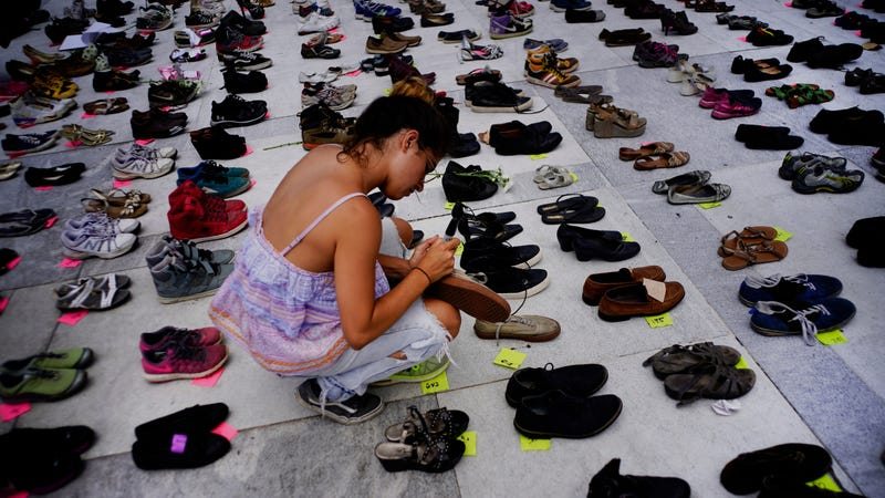 A woman places one of the hundreds of shoes in memory of those killed by Hurricane Maria in front of the Puerto Rico Capitol.