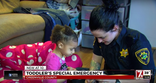 Sheriff's Deputy Martha Lohnes takes a break to play with a little girl who dialed 911 for hep with her pants.WSPA screenshot