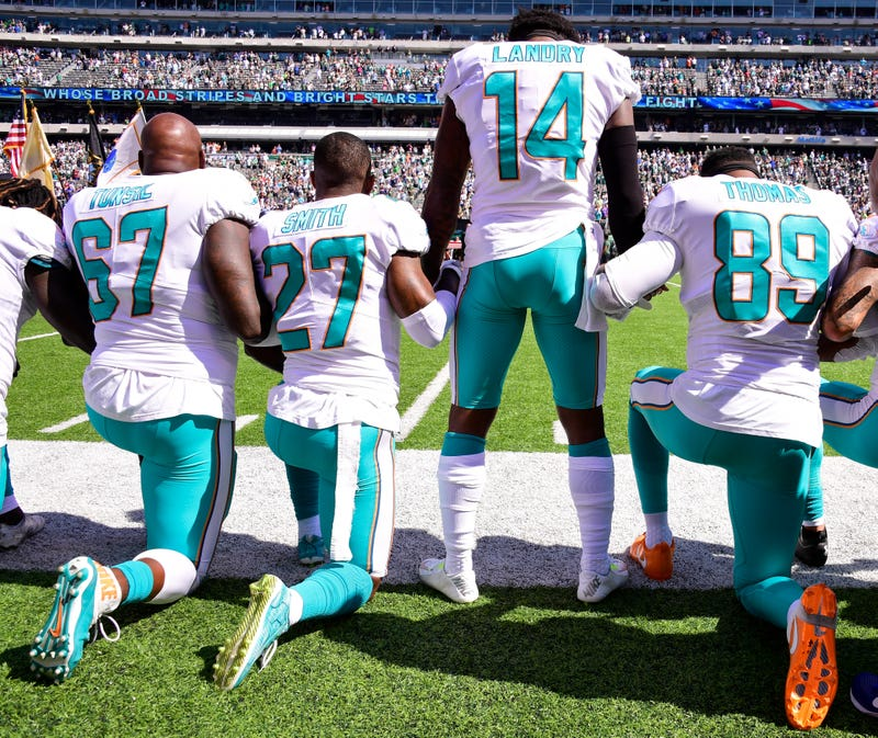 Laremy Tunsil, No. 67, Maurice Smith, No. 27, and Julius Thomas, No. 89, kneel beside Jarvis Landry, No. 14, of the Miami Dolphins during the national anthem prior to an NFL game against the New York Jets at MetLife Stadium on Sept. 24, 2017, in East Rutherford, N.J.