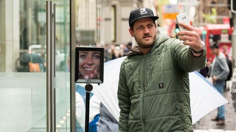 Illustration for article titled Una mujer hace cola para comprar el iPhone 6s mediante un robot de telepresencia