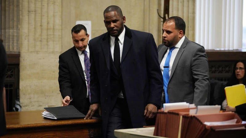 R. Kelly (center) appears in court in Chicago May 7, 2019, on sex assault charges he faces. On May 30, 2019, prosecutors hit the singer with a whole new slate of sex abuse charges.