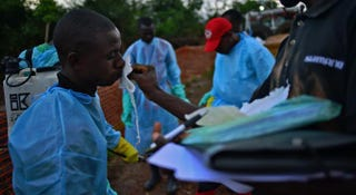 Sierra Leonese government burial team members are disinfected after loading the bodies of Ebola victims onto a truck at the Doctors Without Borders facility in Kailahun on Aug. 14, 2014. CARL DE SOUZA/AFP/Getty Images