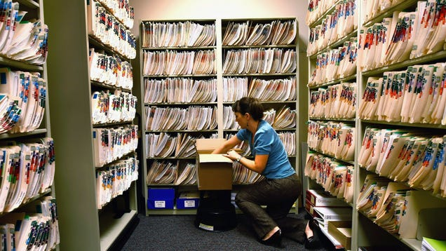 A picture of a healthcare staff person looking through paper health records.