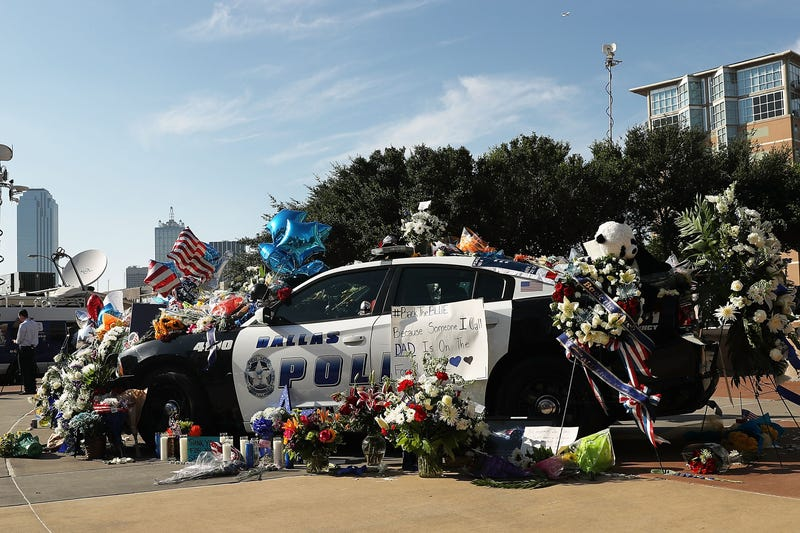 People write condolence notes and lay flowers at a growing memorial in front of the Dallas police headquarters on July 8, 2016, near the area that is still an active crime scene in downtown Dallas following the deaths of five police officers.Spencer Platt/Getty Images