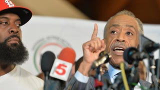 Michael Brown Sr. (left) listens as the Rev. Al Sharpton speaks to the media during a press conference at Greater St. Mark Church in Dellwood, Mo., Nov. 25, 2014.Michael B. Thomas/AFP/Getty Images