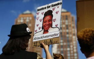 A woman holds a poster bearing the portrait of Sandra Bland, a 28-year-old black woman who died while in police custody in Texas, during a memorial rally in New York Aug. 9, 2015, for Michael Brown, the unarmed teen killed by police in Ferguson, Mo.KENA BETANCUR/AFP/Getty Images