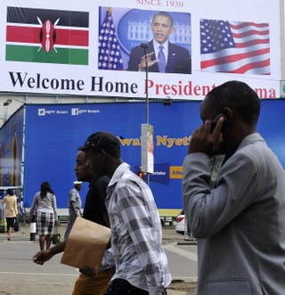Men walk past a billboard in Nairobi, Kenya, July 22, 2015, welcoming President Barack Obama ahead of his visit. Obama will make his first presidential pilgrimage to his father's homeland of Kenya as part of his fourth visit to sub-Saharan Africa.SIMON MAINA/AFP/Getty Images