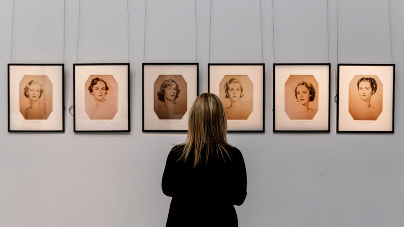A Sotheby's staffer in front of portraits of the Mitford sisters from the collection of Deborah Cavendish, Duchess of Devonshire. Photo via Getty.
