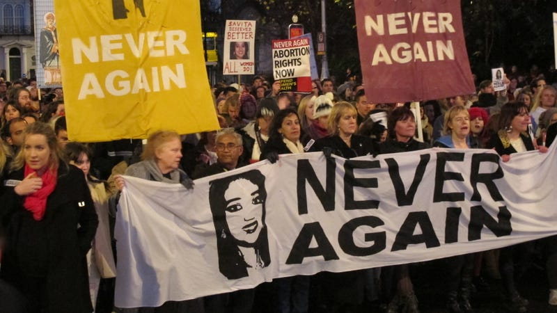 Abortion rights protestors marching with images of Savita Halappanavar in Dublin in 2012. Photo via AP Images.