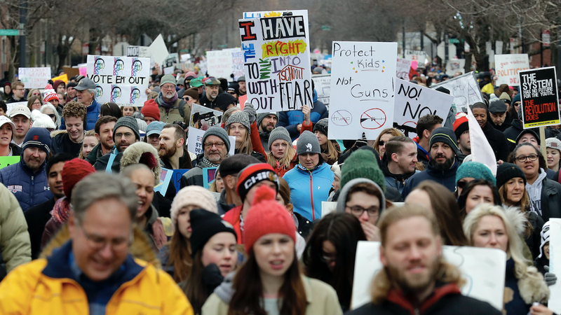 """Demonstrators walk through on the West Washington Blvd during a """"March for Our Lives"""" rally in support of gun control, Saturday, March 24, 2018, in Chicago."""