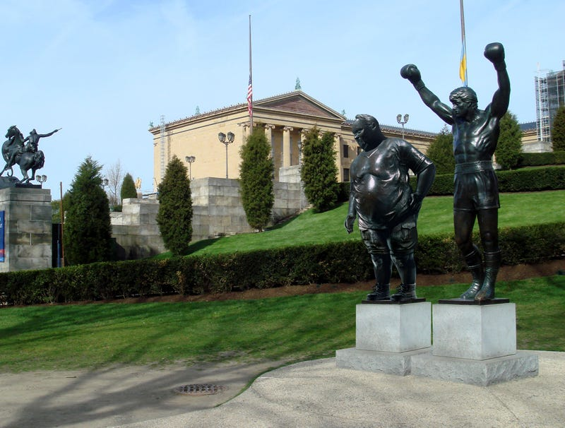 Illustration for article titled Philadelphia Museum Of Art Erects Statue Of Overweight Tourist Posing Next To Rocky Statue