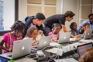 Volunteers work with young girls during a Black Girls Code workshop.Black Girls Code