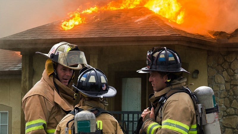 Firefighters talking outside of a burning house.