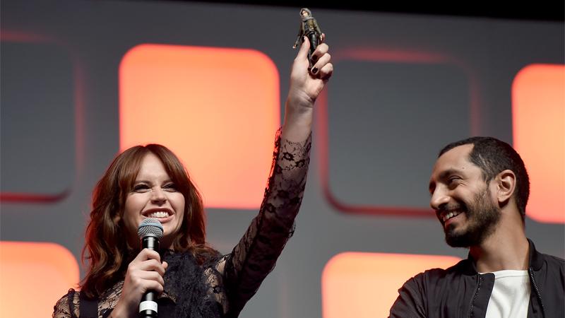 Felicity Jones proudly holds her Jyn Erso action figure aloft at Star Wars Celebration.