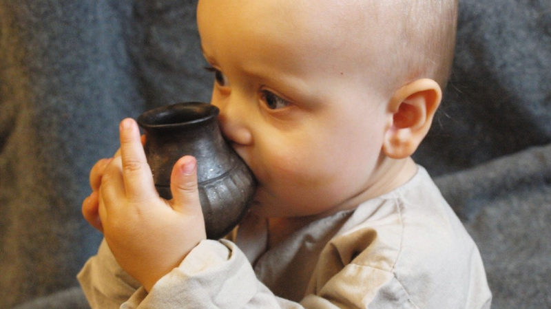 An infant drinks from a reconstructed feeding vessel similar to the ones analyzed in the new study.