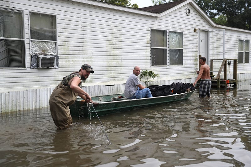 Billy Blazier, Randy Diez Jr. and Tray Blazier check in on Billy Blazier's flooded home Aug. 18, 2016, in Sorrento, La.Joe Raedle/Getty Images