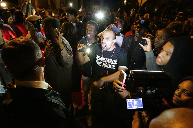 Bassem Masri, center, a man who has live streamed many of the protests in Ferguson, Mo., confronts a St. Louis police officer at the intersection of Shaw Boulevard and Klemm Street as protesters gather at the scene of a fatal police officer-involved shooting on Wednesday, Oct. 8, 2014.