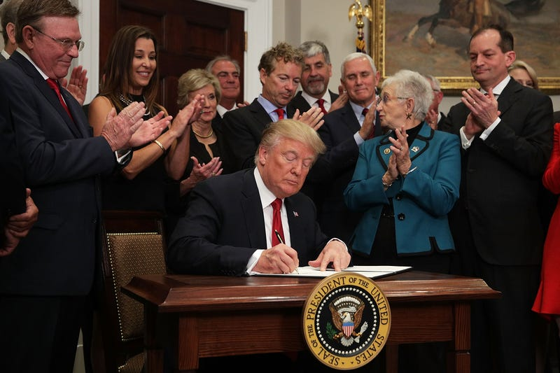 President Donald Trump signs an executive order to loosen restrictions on the Affordable Care Act in the Roosevelt Room of the White House in Washington, D.C., on Oct. 12, 2017.  (Alex Wong/Getty Images)