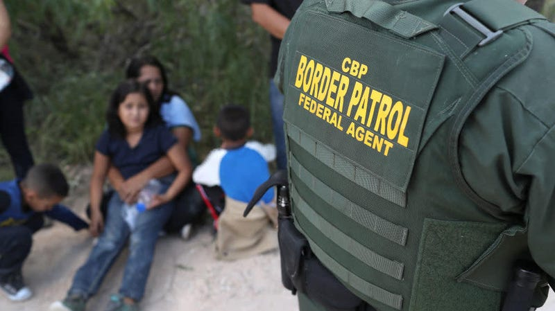 Central American asylum seekers wait as U.S. Border Patrol agents take them into custody on June 12, 2018, near McAllen, Texas.