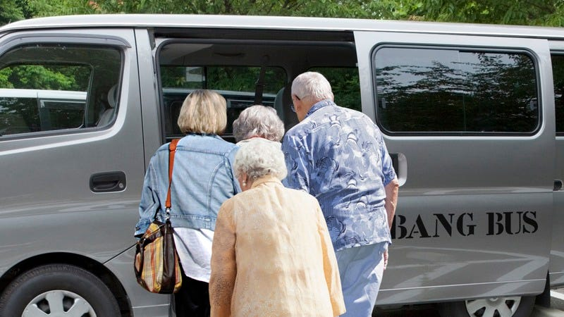 Elderly people stepping into the Bang Bus.